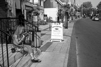 Reading in the street, Ste-Anne-de-Bellevue, Quebec, Canada